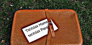 """Brauner Koffer mit Zettel """"tschüss Mama, tschüss Papa"""""""